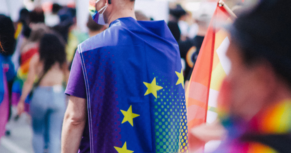 Back of man in outdoor crowd wearing the EU flag as a cape