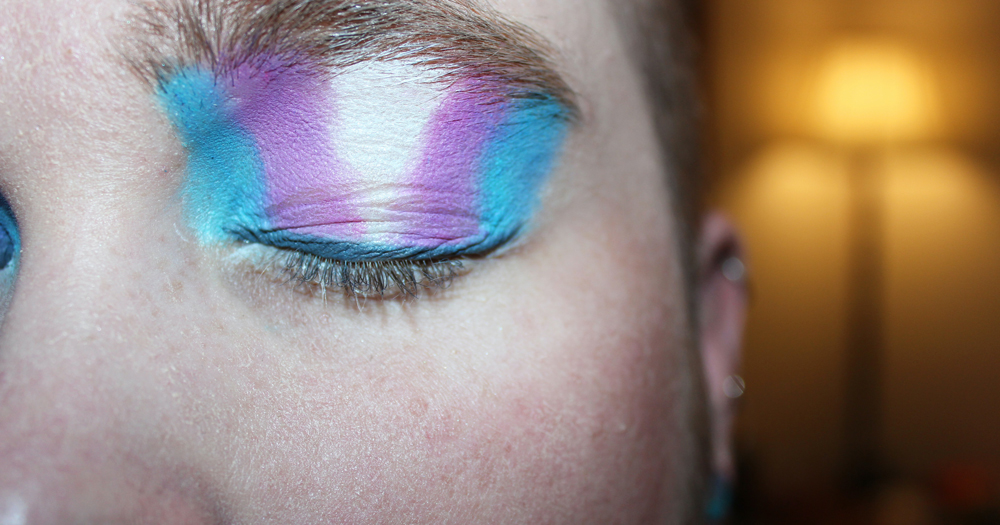 Trans Teens Ireland image of persons closed eye with make up the colours of the trans flag