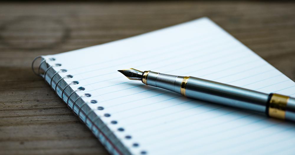 A pen lying across an empty writing pad