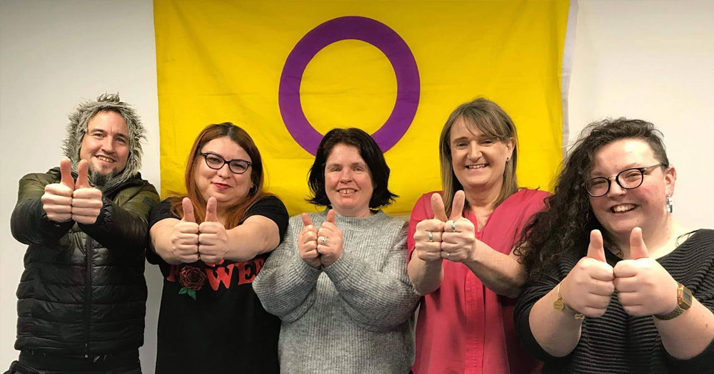 Photo of Intersex Ireland team standing in front of the intersex flag, yellow with a purple circle