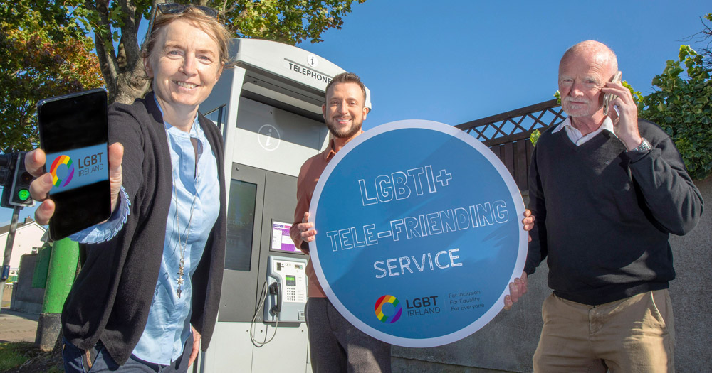 Three people standing beside a payphone. Woman on left is holding a mobile phone to the camera. man in the middle is holding a sign which reads LGBGTI+ Tele-Friending Service. Second man on right is holding a mobile phone to his cheek.